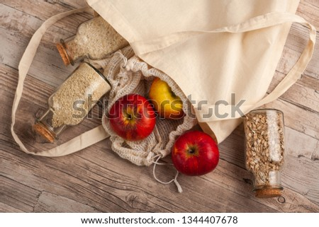 Natural, plastic free recycled textile produce bag for carrying fruit or vegetables on a wooden surface. Reusable cotton textile bags and glass small containers for zero waste shopping or storage. #1344407678