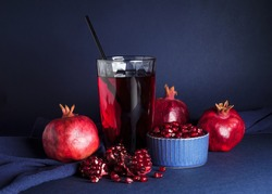 Natural pomegranate juice in a glass with ripe pomegranate fruit on a blue background. This is healthy low-calorie product, an antioxidant and phytonutrient, beneficial for dietary menu.