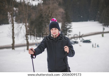 natural portrait of a young ambitious man standing on top of a mountain in the Beskydy Mountains of the Czech Republic, Europe. A man aged 20-24 in a winter hat looking at camera. Foto stock ©