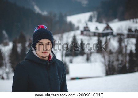 natural portrait of a young ambitious man standing on top of a mountain in the Beskydy Mountains of the Czech Republic, Europe. A man aged 20-24 in a winter hat overlooking the valley. Foto stock ©