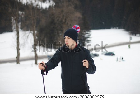 Natural portrait of a young ambitious man standing on top of a mountain with trekking poles in the Beskydy Mountains of the Czech Republic, Europe. A man aged 20-24 in a winter hat looking at valley. Foto stock ©