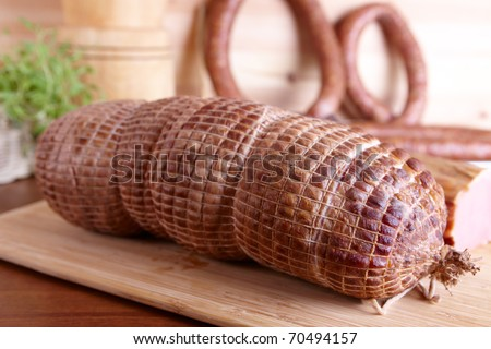 Natural prepared slow food cured pork shoulder which looks similar to ham, smoked pork sirloin, and ring-shaped sausage in the background all on the wooden board with herbs