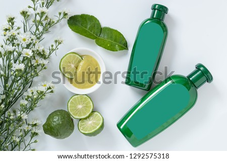 natural products for hair concept. two size of green plastic bottle with blank label contain herbal bergamot shampoo decorate with slide kaffir limes ,kaffir leaf and white flowers on white background