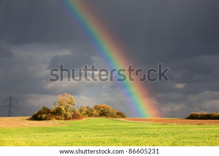 Natural rainbow over green field and dark sky