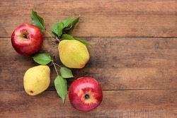 Natural red apples and yellow pears with leaves on old wooden table. Wooden background with fresh organic fruits. Autumn harvest. Flat lay. Rustic style. Copy space. Selective focus