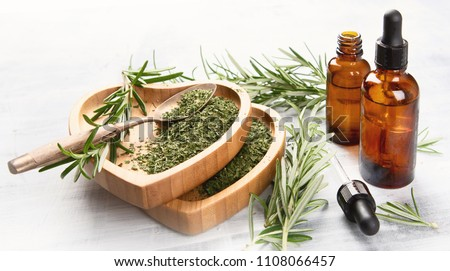 Natural rosemary essential oil with fresh rosemary twigs