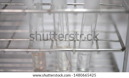 Natural rubber that is dissolved with chemicals in test tubes in a chemical laboratory.
