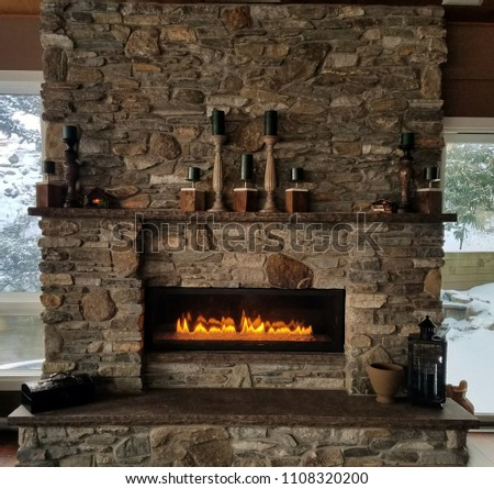 Natural, Rustic, Stone Fireplace With Roaring Flames in Winter