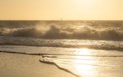 Natural scene of orange light from sunset over big waves hit rocks to make splashing water and bubble at Baker beach, San Francisco, California, USA.