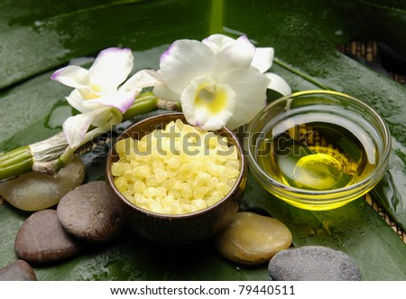 Natural sea bath salt in wood bowl with orchid and stones on leaf