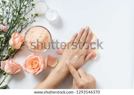 natural skincare concept. woman apply white cream on her hands on white background with jar of cosmetic cream, salt spa scrub ,rose and  white flowers with copy space