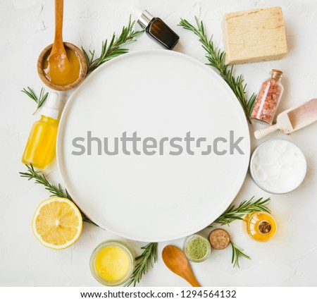 Natural skincare cosmetics products with oils, manuka honey, lemon, rosemary, bath salt , soap, salve balm with copy space round white plate in the middle #1294564132