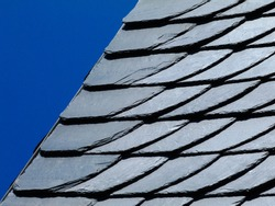 natural slate mineral tile covered roof detail. natural construction materials concept. building industry and organic architecture. fish scale pattern. rough edges.