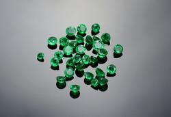 Natural small round shaped muzo mine colombian emeralds for making jewelry in semidark gray gradient background. Closeup makro gemstones.