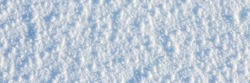 Natural snow texture. The surface of an icy snow crust. Snowy ground. Winter background with snow patterns. Perfect for Christmas and New Year design. Closeup top view.