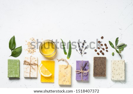 Natural soap bars with ingredients. Aloe, lavender, eucalyptus, olive, honey, coffee, tee tree oil and oat soaps. Flat lay image with copy space.