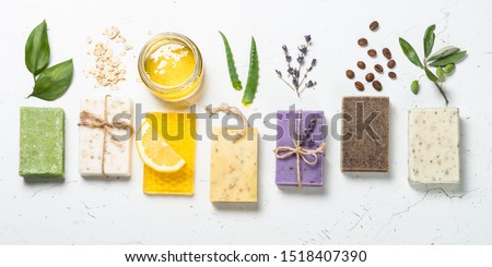 Natural soap bars with ingredients. Aloe, lavender, eucalyptus, olive, honey, coffee, tee tree oil and oat soaps. Top view with copy space.