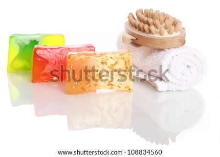 Natural soap with white towel and wooden brush over white background