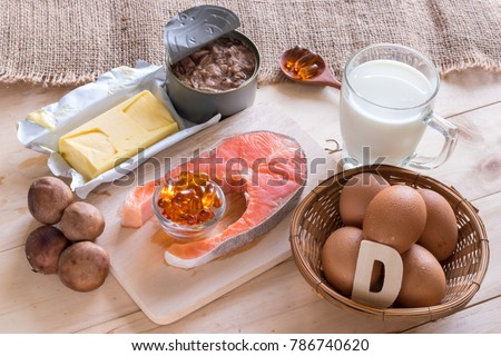Natural source of vitamin D in Salmon, eggs, mushroom, fortified milk, margarine, canned tuna and fish oil capsule on wooden texture and background, healthcare and supplemental concept