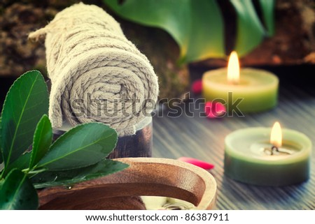 Natural spa setting with rose water and towel.