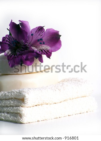 Natural spa soap, flowers and folded towels.