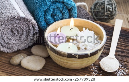Natural Spa with Burning Candles in the Water on Wooden Background with Towels,Bath Salt and Flower