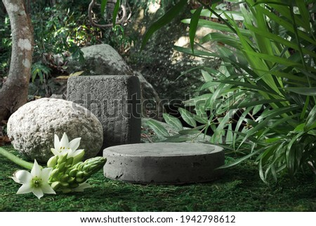 Natural stone and concrete podium in tropical forest with flowers. Empty showcase for packaging product presentation. Background for cosmetic products, scene with green leaves. Mock up pedestal.