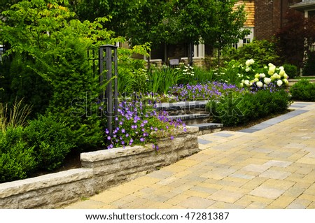 Natural stone landscaping in front of a house with lush green garden