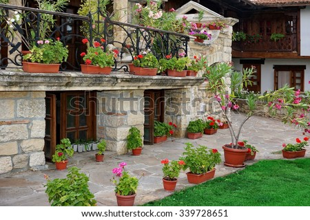 Natural Stone Landscaping In The Backyard And Many Flowers In The Pot