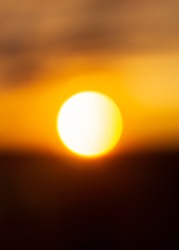 Natural sun background of bright white hot solar ball at sunset