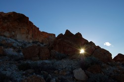 Natural sunburst or sun flare shinning through a small tunnel or aperture between large rocks, on the side of a hill. Sunburst silhouetted against a dark foreground to show the natural light rays.