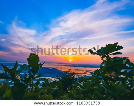 Natural Sunset Photo from between of a leaf.Bright Dramatic Sky And Dark Ground. Countryside Landscape Under Scenic Colorful Sky At Sunset Dawn Sunrise. Sun Over Skyline, Horizon. Warm Colors
