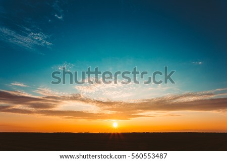 Natural Sunset Sunrise Over Field Or Meadow. Bright Dramatic Sky And Dark Ground. Countryside Landscape Under Scenic Colorful Sky At Sunset Dawn Sunrise. Sun Over Skyline, Horizon. Warm Colours. #560553487