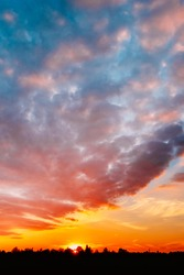 Natural Sunset, Sunrise Over Forest. Bright Dramatic Sky And Dark Ground. Countryside Landscape Under Scenic Summer Dramatic Sky In Sunset Dawn Sunrise. Skyline. Warm Colors.