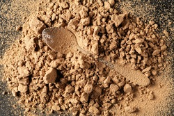 natural, sweet carob powder on the table is scattered, the imprint of a metal spoon