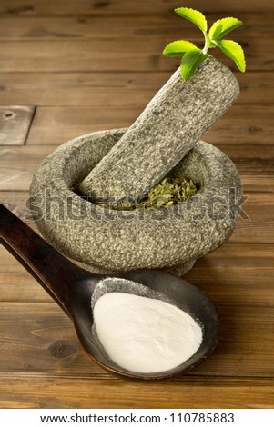 Natural sweetener Stevia as white powder and dried herb leaves