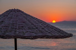 Natural textured straw parasol at seaside with orange sun and sea background at dawn. Umbrella as object