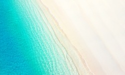 Natural textured summer background for vacation. White golden sand on the beach and turquoise water of the ocean sea with the incoming wave, copy space.