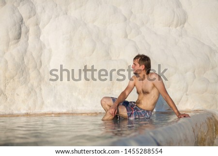 Natural travertine pools and terraces in Pamukkale. Cotton castle in southwestern Turkey. Young man sitting at the pool in natural bath. Beautiful man looks Pamukkale (Cotton Castle) #1455288554