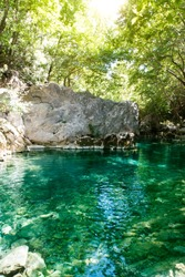 Natural turquoise pool in the deep forest. Hidden brook deep inside the canyon.