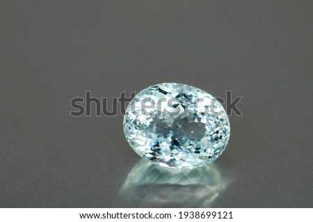 Natural unheated sky blue big topaz oval faceted gemstone. Clean, transparent, huge, sparkling treasure. Gray backgroung. Many facets, cut in Thailand. Original from Brazil. Zdjęcia stock ©