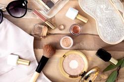 Natural vegan make up flat lay on wooden background - eye shadows, brushes, lipstick, blouse, sun glassses.