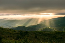 Natural view of sunrays and sunshine over the mountains valley during sunset. Nature summer landscape.