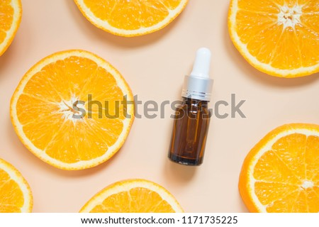 Natural vitamin c serum, skincare, essential oil products. Cosmetic brown glass vial w/ dropper and fresh juicy orange fruit slice on orange background. Beauty product branding mock-up. Top view.