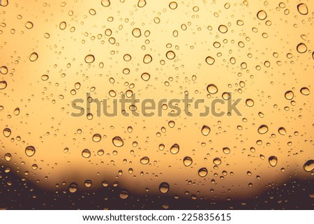Natural water drops on orange colour  window glass background