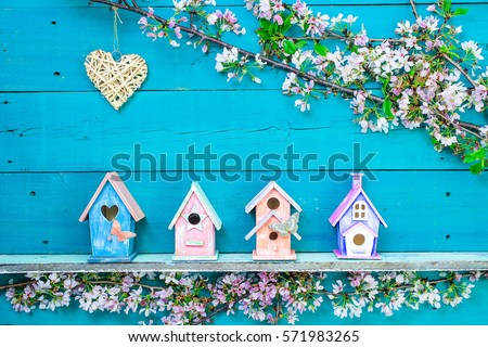 Natural wicker heart hanging over colorful birdhouses with butterfly on shelf by spring tree flowers on antique rustic teal blue wooden background; springtime background with painted wood copy space