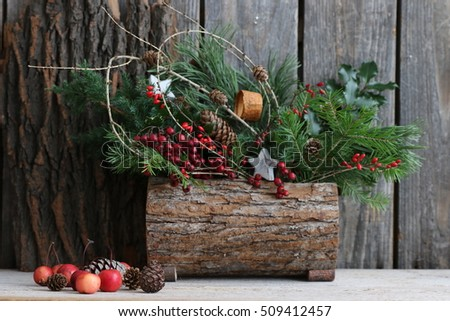 Stock Photo Natural Winter composition, Christmas decoration from pine branches with cones, juniper, holly, barberry, star, pink crab apples, red berries in wooden planter from bark on dark background, daylight