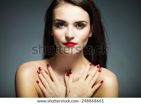 Natural woman face with red nails and lips on dark background