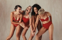 Natural women of all ages celebrating their ageing bodies. Four happy and body positive women having fun while wearing red swimwear against a studio background.