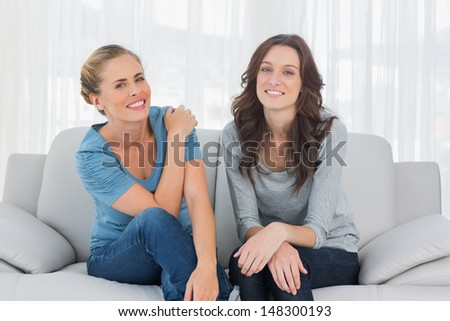 Natural women posing while sitting on the couch looking at camera